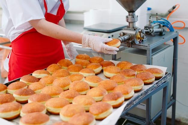 製菓工場でのクリームとジャム入りの美味しいドーナツの製造