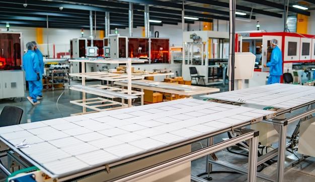 ソーラーパネルの製造、工場で働く男性。太陽光発電パネル工場の特殊機械のクローズアップ