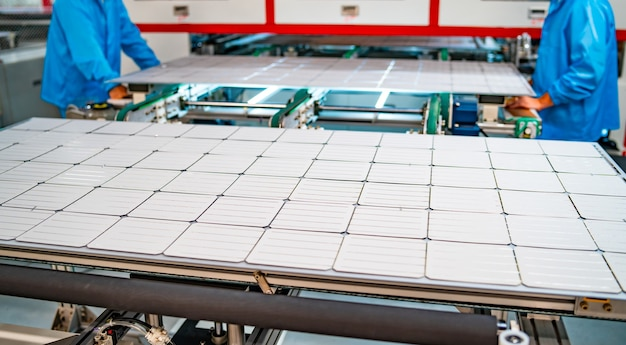 ソーラーパネルの製造、工場で働く男性。太陽光発電パネル工場の重機のクローズアップ。