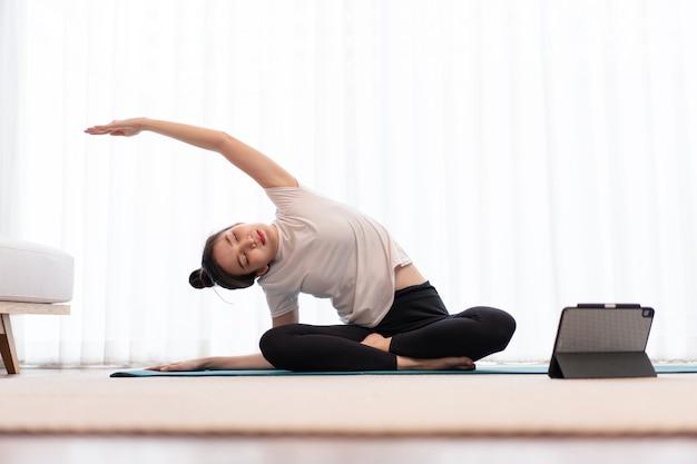 생산적인 활동 개념 흰색 티셔츠를 입은 젊은 성인 여성은 매트 필라테스를 하여 몸의 유연성을 연습합니다.