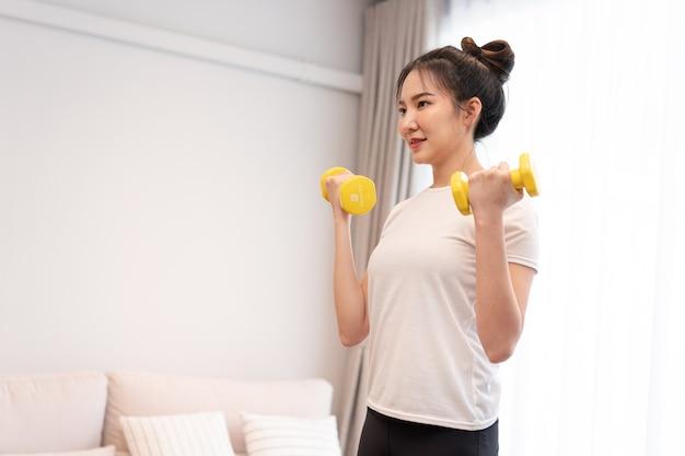 생산적인 활동 개념 흰색 티셔츠를 입은 롤빵을 가진 소녀가 거실에서 오른손으로 노란색 덤벨을 들고 있습니다.