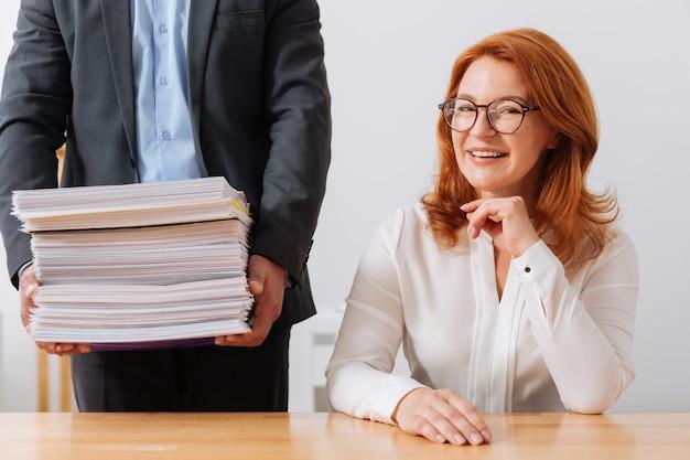 서류 더미를 받아 사무실에서 하루를 시작하는 생산적인 밝은 여성