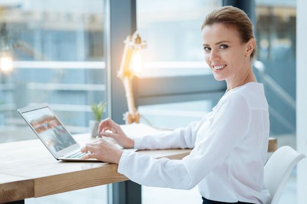生産的な日。明るいランプを使用しながらラップトップで作業し、喜びながらあなたを見ている熟練した秘書のクローズアップ