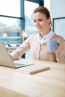 생산적인 날. 노트북을 사용하고 커피를 마시는 동안 테이블에 앉아 긍정적 인 사무실 관리자