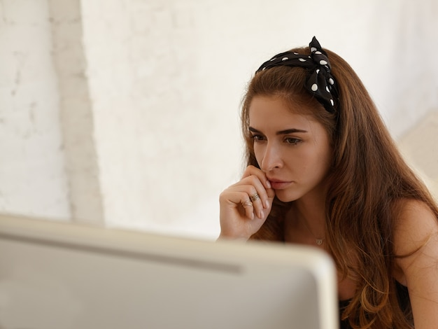 생산적인 직업 개념. 작업 장소에 앉아있는 동안 pc 컴퓨터에서 작업하는 세련된 headscarf를 입고 집중된 백인 젊은 여자의 초상화, 홍보 콘텐츠를위한 공간을 복사합니다.