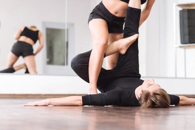 生産的なトレーニング。床に横になり、ダンスパートナーに助けられながら足を上げている素敵な若い男性ダンサー
