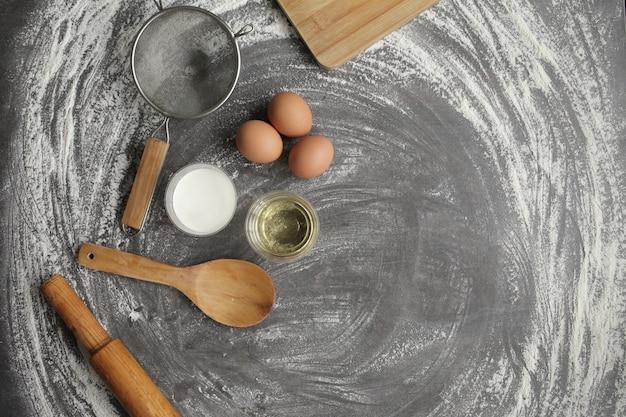 散らばった小麦粉の灰色のテーブルでパンやケーキを焼くための製品とツール