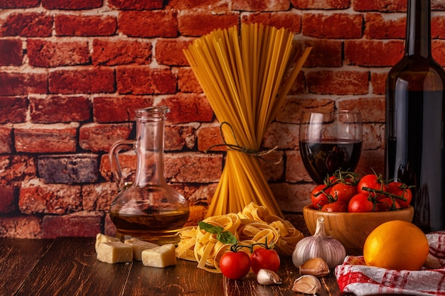 Products for cooking pasta, tomatoes, garlic, olive oil and red wine