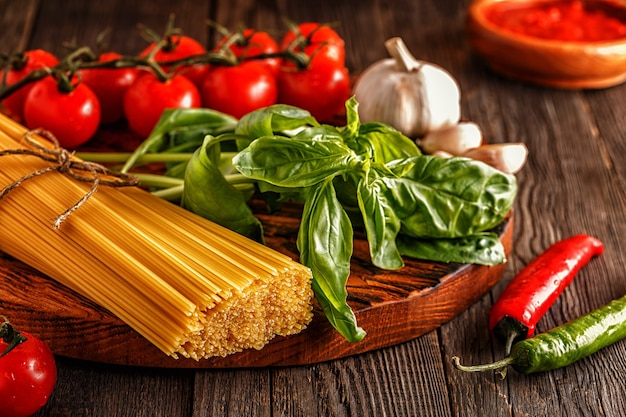 Products for cooking pasta, tomatoes, garlic, pepper, and basil on the old wooden background