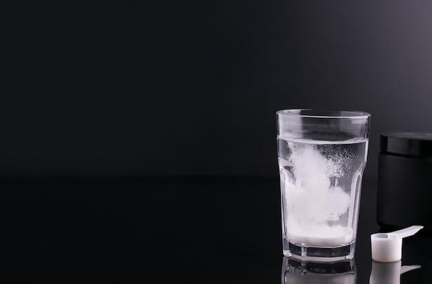 Товары для спортсменов. белый напиток в стакане на черном фоне копией пространства. баннер