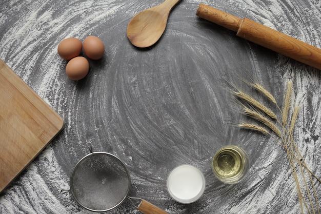 회색 콘크리트 테이블에 빵과 케이크를 굽는 제품 닭고기 달걀, 밀가루, 올리브 오일 및 우유.