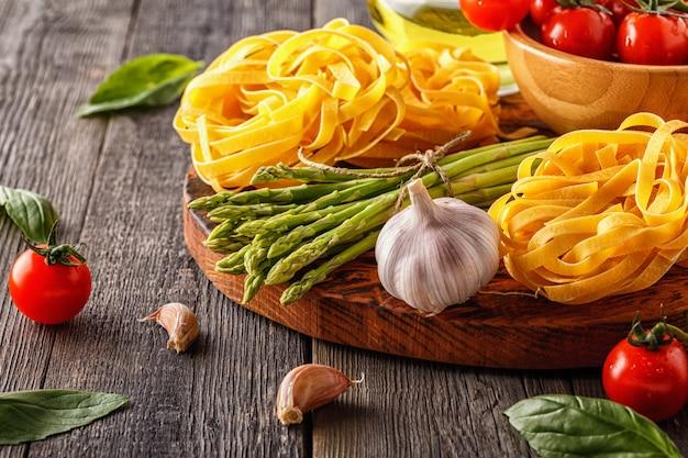 調理用製品-新鮮なアスパラガス、パスタ、オリーブオイル。