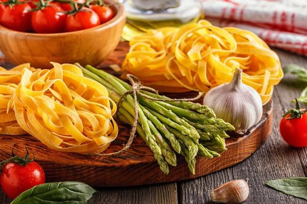 調理用製品。古い木製の背景に新鮮なアスパラガス、パスタ、トマト、ニンニク、オリーブオイル。