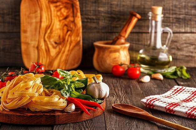 Продукты для приготовления пасты, помидоров, чеснока, перца и базилика на старом деревянном фоне