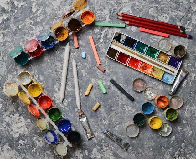 Изделия для рисования на бетонном столе. концепция вдохновения для творчества. разноцветные гуашь, масло, акварельные краски, цветные карандаши, карандаши. вид сверху.