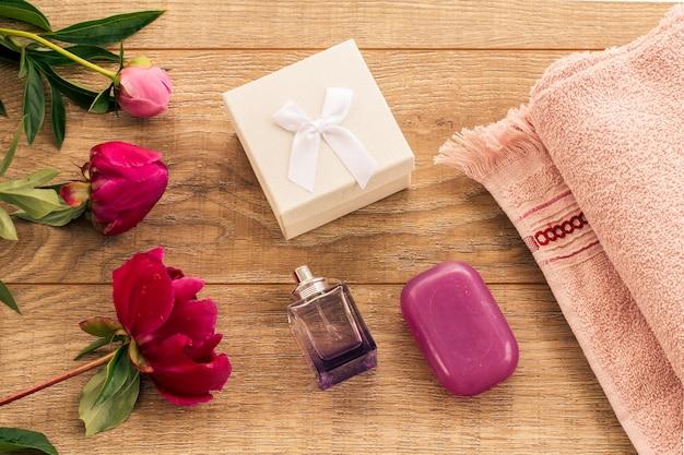 フェイシャルおよびボディケア用の製品。ギフトボックス、香水、石鹸と牡丹の花と木製の背景に柔らかいテリータオル。スパとボディケアセット。休日の挨拶の概念。上面図。