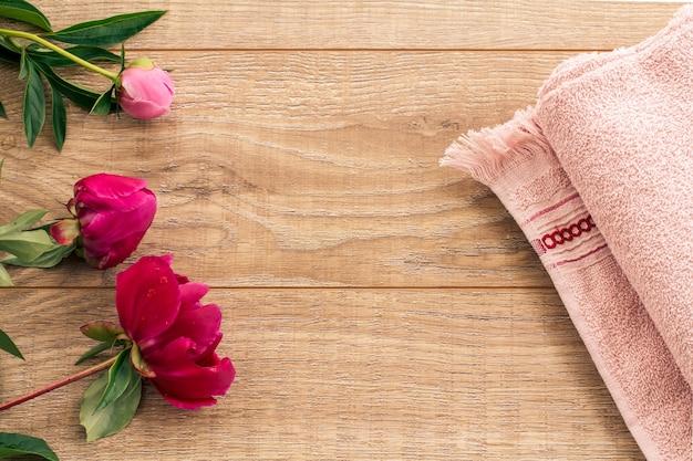 페이셜 및 바디 케어용 제품. 나무 배경에 부드러운 테리 수건과 모란 꽃. 스파 및 바디케어 세트입니다. 평면도.