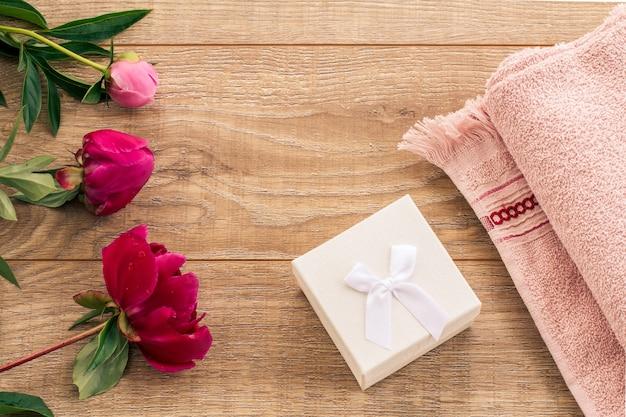 Продукты для ухода за лицом и телом. мягкое махровое полотенце с белой подарочной коробкой и цветами пиона на деревянном фоне. набор для спа и ухода за телом. вид сверху. Premium Фотографии