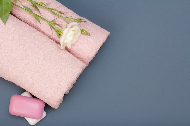 페이셜 및 바디 케어용 제품. 회색 배경에 비누와 꽃이 있는 부드러운 테리 수건. 스파 및 바디 케어 개념입니다. 복사 공간이 있는 상위 뷰입니다.