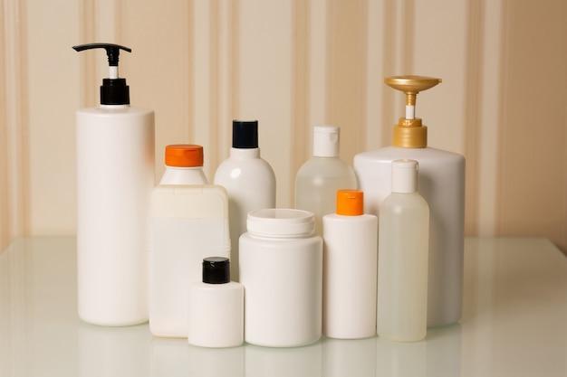 自宅でのヘアケア用製品:ベージュの背景にシャンプー、コンディショナー、マスク、オイル、美容液