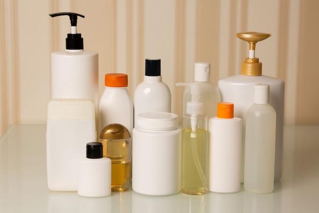 自宅でのヘアトリートメント用製品:ベージュの背景にシャンプー、コンディショナー、マスク、オイル、美容液