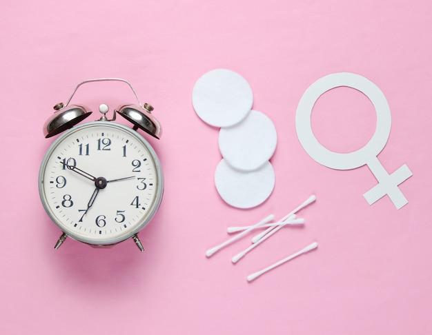 衛生、女性の性別記号、ピンクのパステル調の背景にレトロな目覚まし時計のための製品。