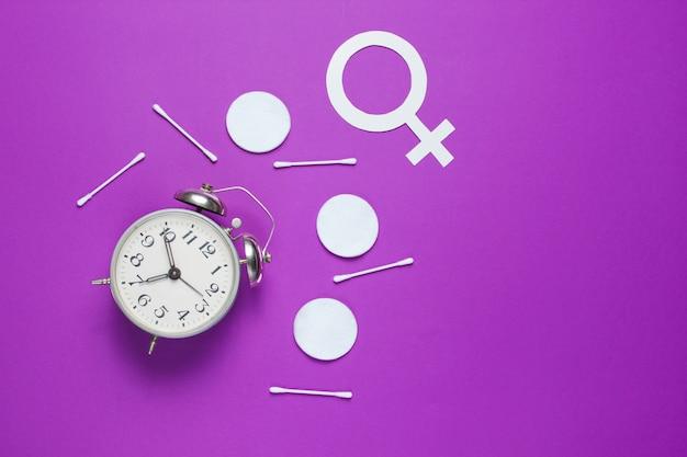 衛生用品、女性の性別記号、レトロな目覚まし時計