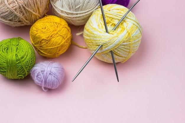 裁縫、編み物用の製品。黄色、緑、紫の糸、ピンクの背景に編み針のボール。テキスト用のスペース。