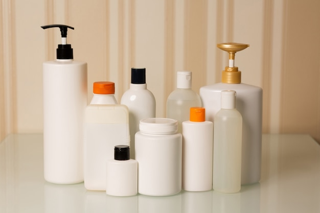 Products for hair care at home: shampoo, conditioner, mask, oil and serum on a beige background