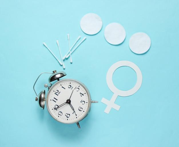 Products for hygiene, female gender symbol, retro alarm clock on blue pastel background