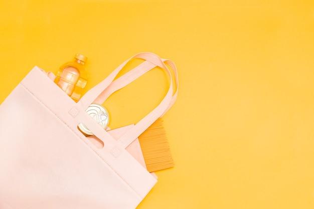 Товары в эко-сумке, вид сверху, на желтом