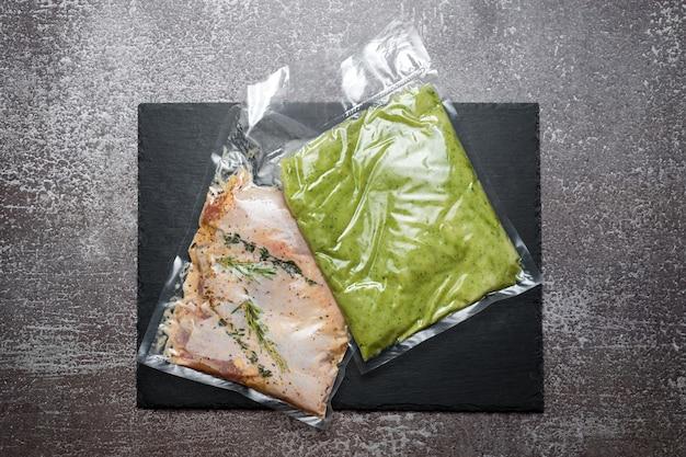 Продукция в вакуумной упаковке на черном грифельном картоне. куриное мясо с зеленью и пюре из стручковой фасоли, продукты в вакуумной упаковке, готовые для приготовления в режиме су-вид. су-вид, новая кухня в условиях карантина.