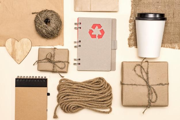Изделия из переработанного крафт-папера и дерева: пакеты, блокнот, одноразовая кофейная чашка, деревянное сердечко, шнур. концепция охраны окружающей среды, утилизации бизнеса. вид сверху