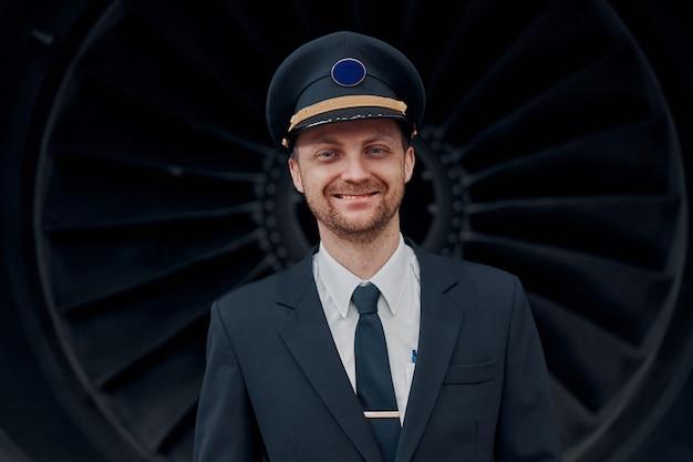 Profesol confident pilot is checking plane in hangar
