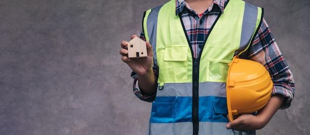 엔지니어가 열심히 일한 후 현장에 휴식하기 전에 안전모와 목조 주택을 들고있는 작업자의 전문가