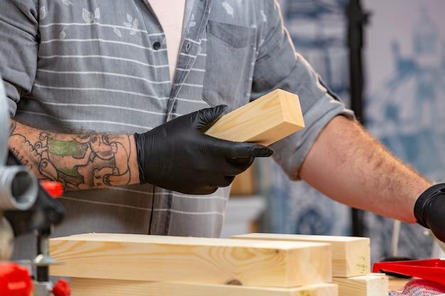 職業、大工仕事、木工、人々のコンセプト-大工のワークショップで木の板での作業