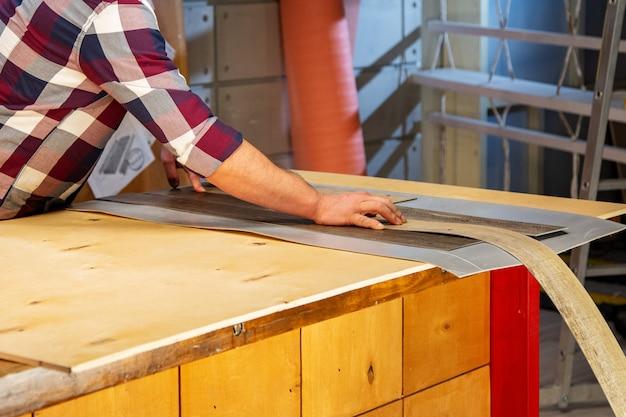 職業、大工仕事、木工および人々のコンセプト-木の板で働く大工