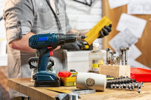 Profession, carpentry, woodwork and people concept - carpenter with electric drill drilling wood plank at workshop