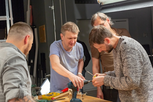 Profession, carpentry, woodwork and people concept, carpenters prepares the drill for work