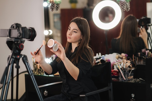 Profession make up artist woman reviewing beauty products on a videoo blog at beauty studio. woman
