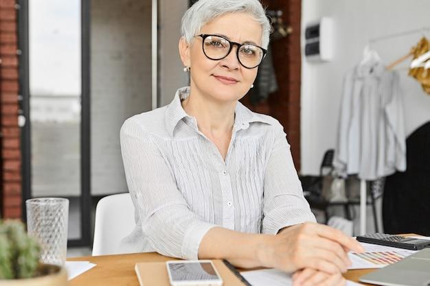 Концепция профессии, занятия, работы и карьеры. уверенная в себе стильная современная женщина-маркетолог лет шестидесяти, работающая в офисе с ноутбуком, мобильным телефоном и калькулятором в очках