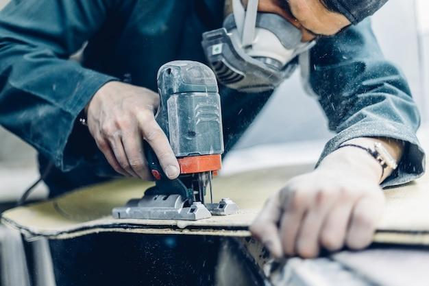 Профессия, люди, плотницкие работы, эмоции и концепция людей. плотник вырезает доску электрическим лобзиком. производство скейтбордов. у него есть защитная одежда и маска. 4k