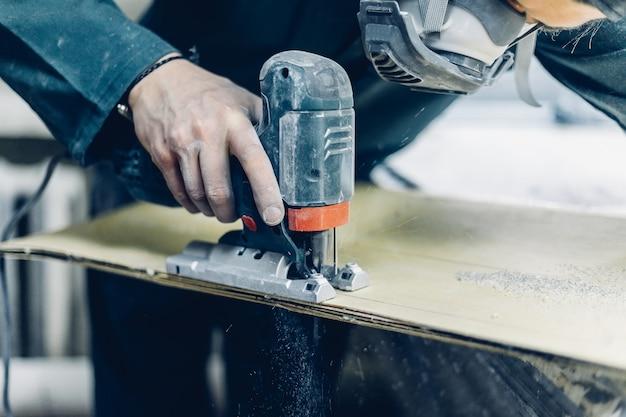 직업, 사람, 목공, 감정, 그리고 사람 개념 - 목수는 전기 퍼즐로 판자를 자릅니다. 스케이트보드 제조. 그는 보호복과 마스크를 가지고 있습니다. 4k