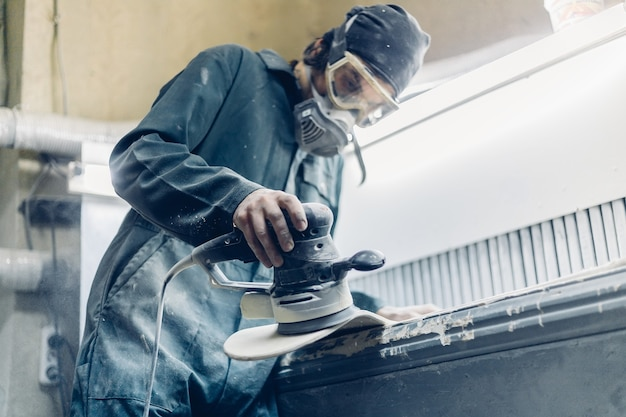 Профессия, люди, плотницкие работы, эмоции и концепция людей. плотник вырезает доску электрическим лобзиком. производство скейтбордов. у него есть защитная одежда и маска.