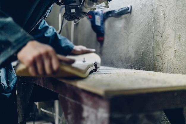 Профессия, плотницкие работы, эмоции и концепция людей - молодой ремесленник шлифует палубу, меняя фокус с помощью шлифовального инструмента. производство скейтбордов. у него есть защитная одежда и маска.
