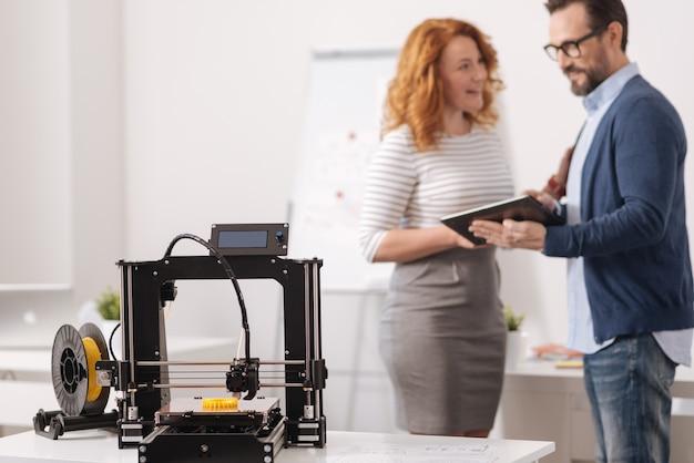 백그라운드에서 서로 이야기하는 좋은 기쁘게 동료와 함께 테이블에 서있는 전문 3d 프린터