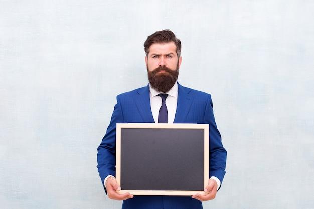 プロのアカデミー。ビジネスマンは学校の黒板を保持します。ビジネス教育。ビジネスを勉強します。教育と研究。教育コース。オンライン教育。いつでもどこでも学び、スペースをコピーします。
