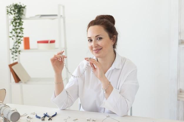 スタジオワークショップで手作りジュエリーを作るプロのアクセサリーデザイナー。ファッション、創造性