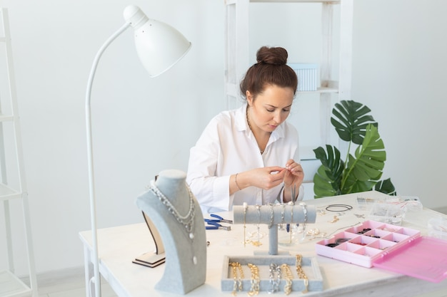 스튜디오 워크샵에서 수제 보석을 만드는 전문 액세서리 디자이너