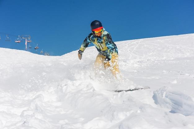山の斜面を下る明るいスポーツウェアでプロのアクティブなスノーボーダー